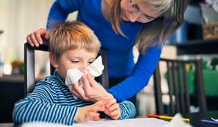 Мать помогает ее сморкающемуся сыну