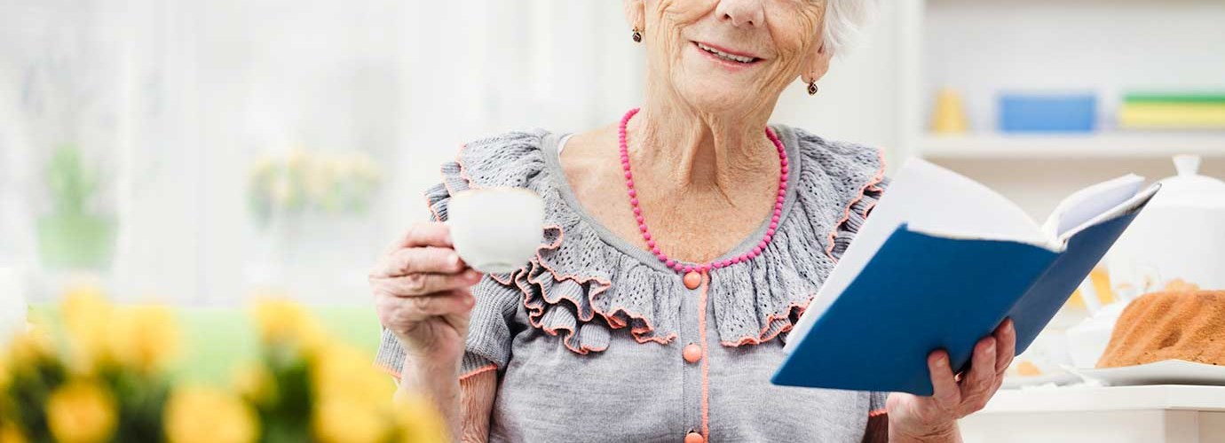 Пожилая женщина сидит на диване, держа книгу и чашку