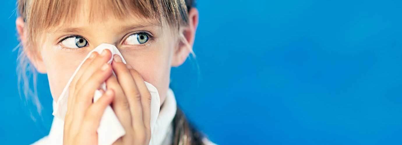 Девочка с простудой держит бумажную салфетку перед носом
