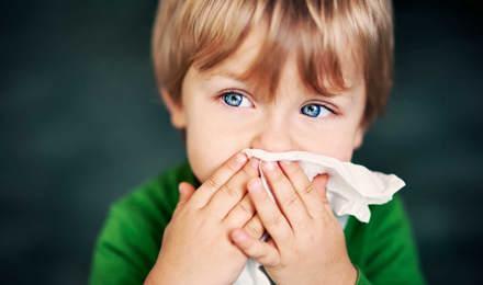 Мальчик с аллергией на пыль держит бумажную салфетку перед его носом