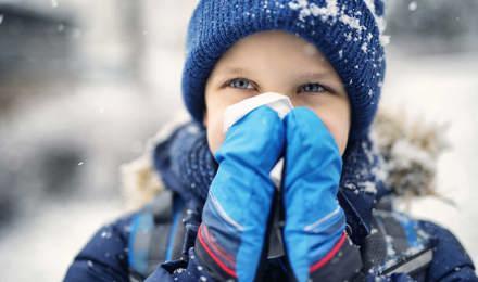 Маленький ребенок в зимней одежде сморкается