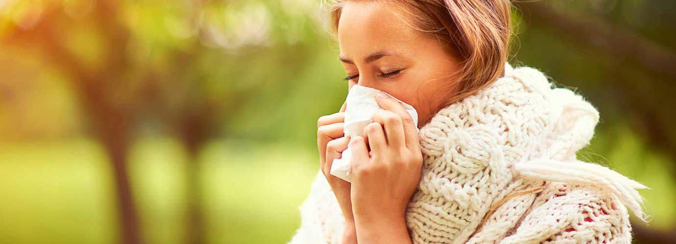 Молодая женщина в джемпере сидит в парке, чихая, и думает о причинах ее сенной лихорадки