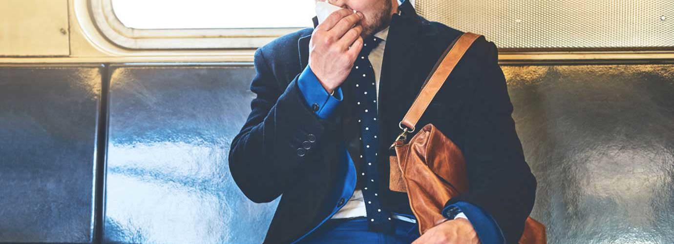 Человек, одетый в костюм, сидит в вагоне поезда и сморкается