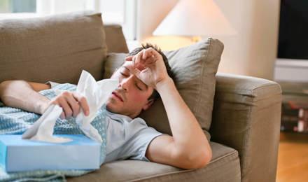 Человек лежит на диване с гриппом, держа салфетки