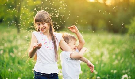 Брат и сестра играют на поле одуванчиков, окруженные пыльцой