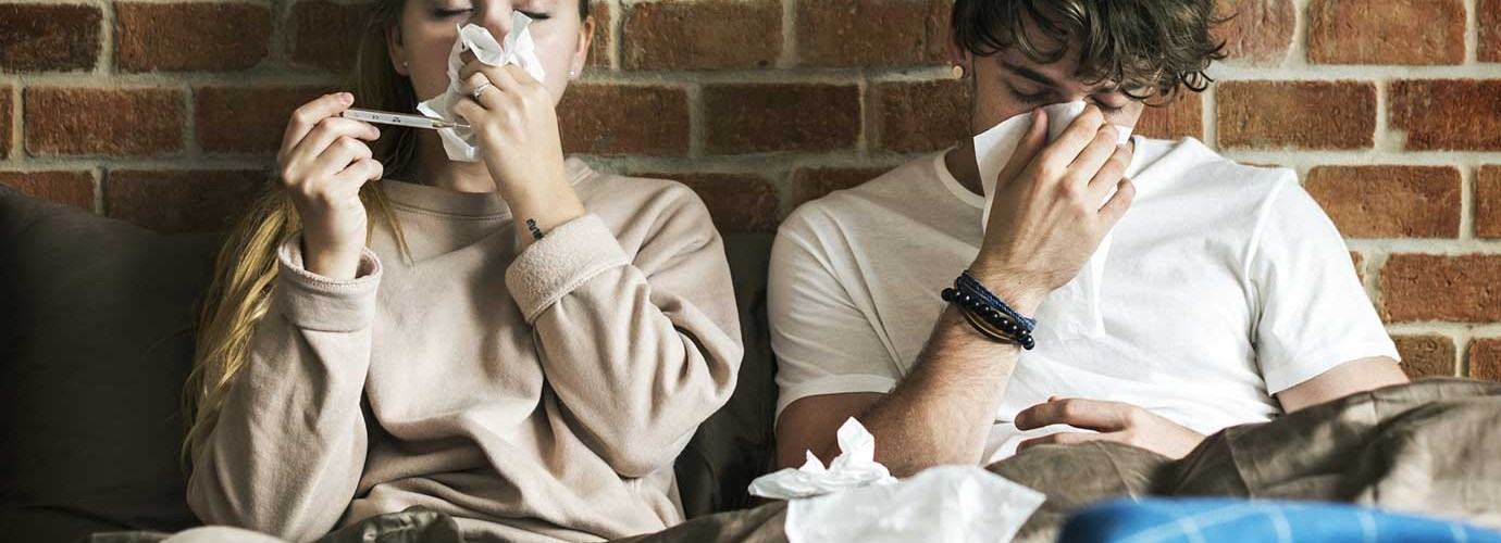 Две молодых людей сидят под одеялами и чихают в салфетки с фоном кирпичной стены