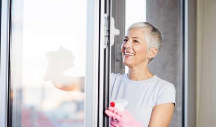 Зрелая женщина чистит окна изнутри
