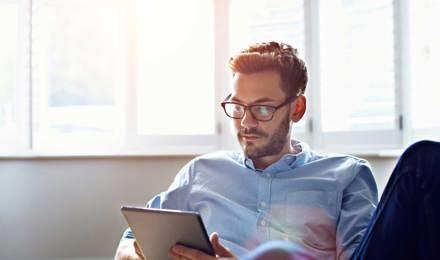Человек в очках сидит на диване, глядя на цифровой планшет