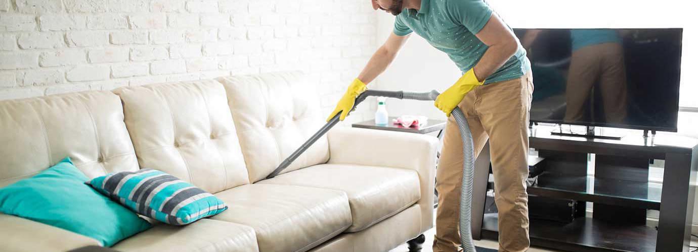 Человек чистит белую ткань дивана с пылесосом