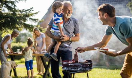 Человек готовит барбекю на заднем дворе семьи