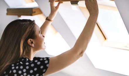 Egy nő nyitja az ablakokat, hogy levegőt engedjen a szobába