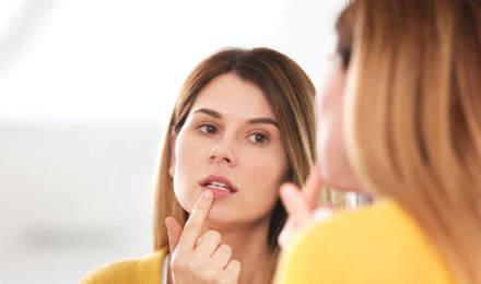 Nő kezeli a herpeszt a tükör előtt
