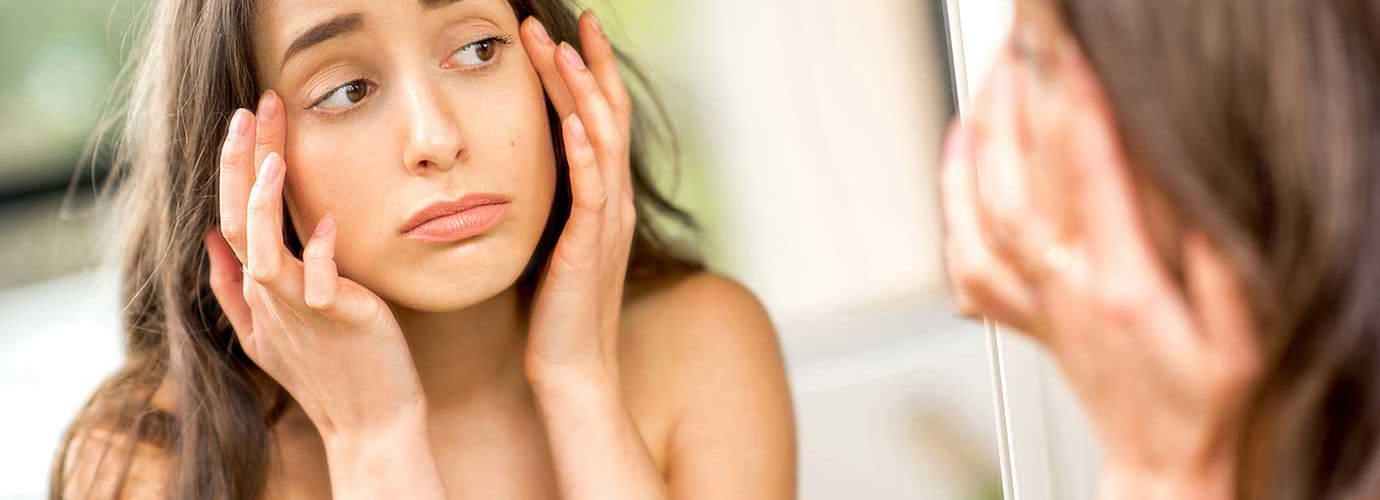 Tinédzser ellenőrzi az allergiától duzzadt szemeit a tükörben