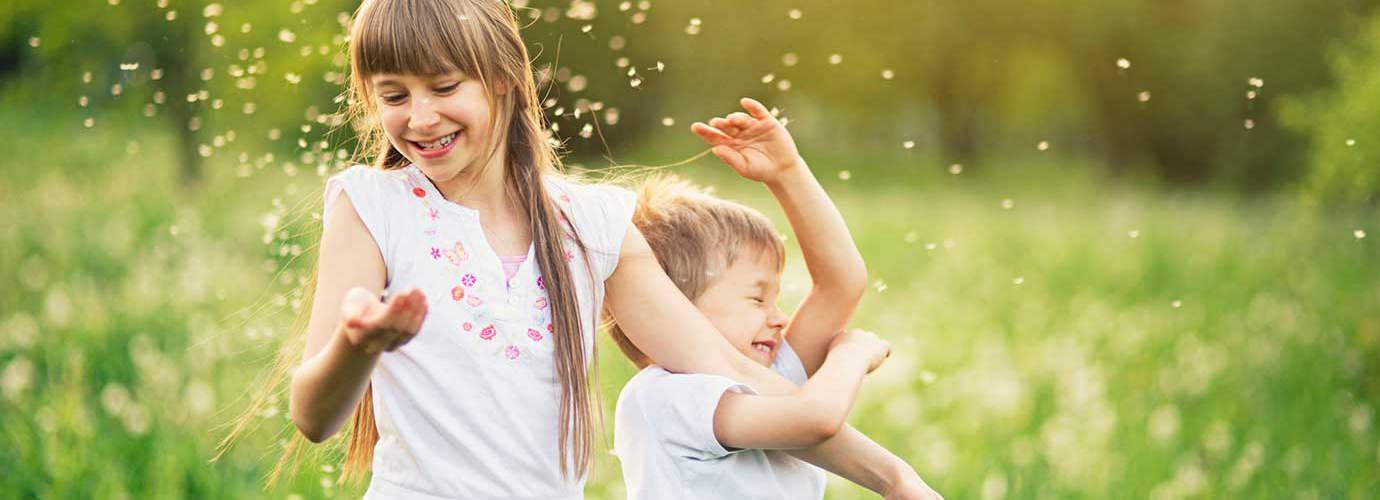 Fiú- és lánytestvér játszik a pitypangmezőn pollennel körülvéve