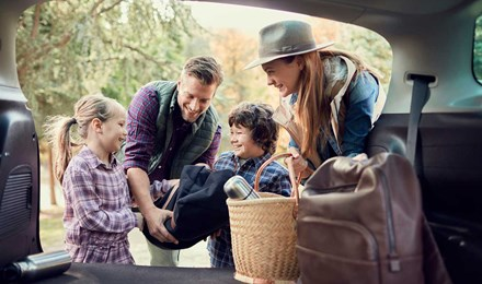 Fiatal család pakol kempingezéshez a gyerekekkel