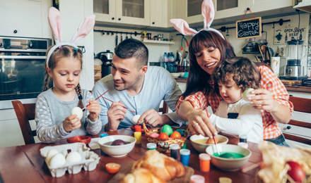 Család ül a konyhaasztalnál húsvéti tojást festve