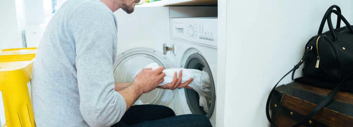Muškarac stavlja odjeću u perilicu rublja