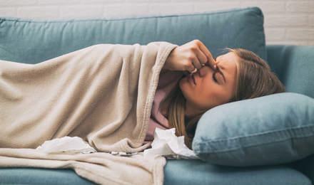 Žena leži na plavom kauču i osjeća da je bole sinusi
