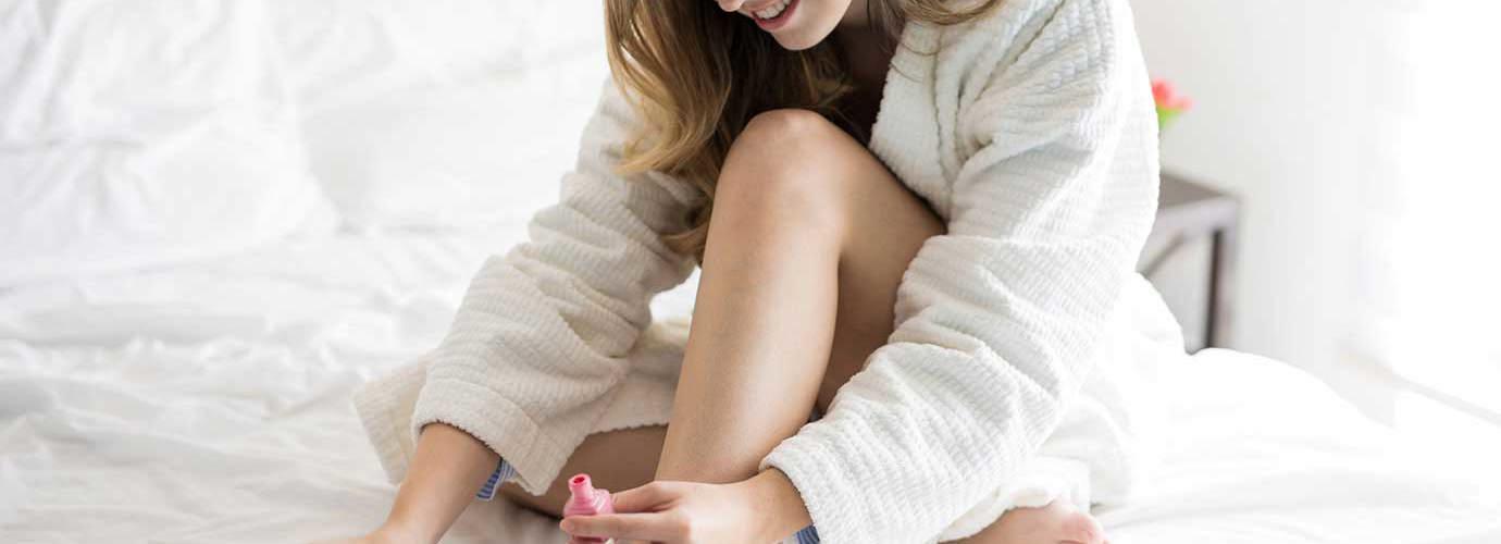 Mlada žena sjedi na bijelom krevetu i lakira nokte na nogama