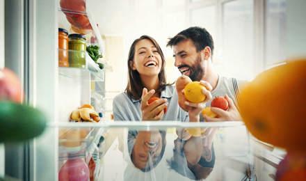 Un cuplu luând niște fructe și legume din frigider