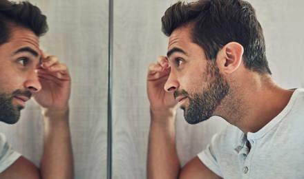 Un bărbat care se uită la el în oglindă