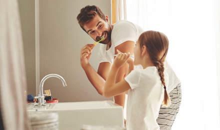 Muž a jeho mladá dcera se učí šetřit vodou při čistění zubů v koupelně