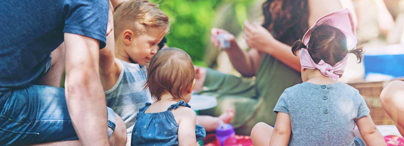 Skupina dospělých a dětí sedící na dece při rodinném pikniku