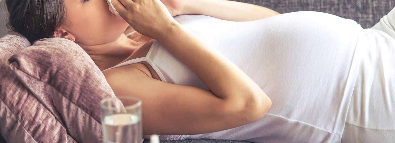 Една млада жена, която е бременна с настинка на дивана.