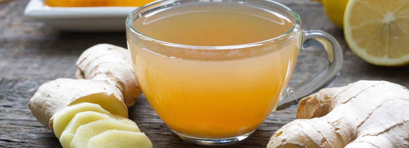 Цялата и нарязан джинджифил, мед, лимон и една чаша от сместа седна на една дървена маса