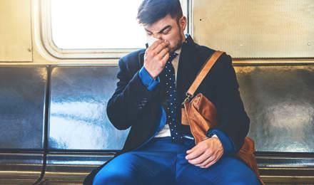 Един човек, облечен в костюм седеше на превоз с влак изсекна
