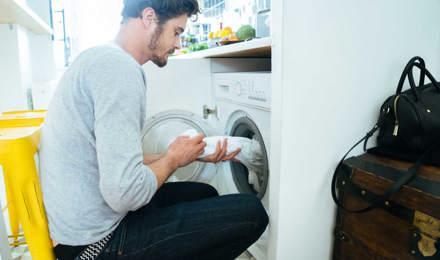 Man пускането дрехи в пералнята