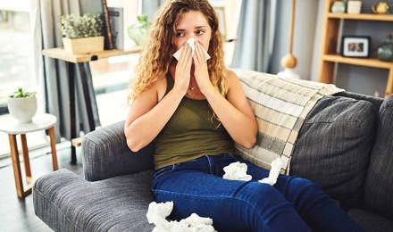 Femeie cu simptome de alergie sau răceală își suflă nasul