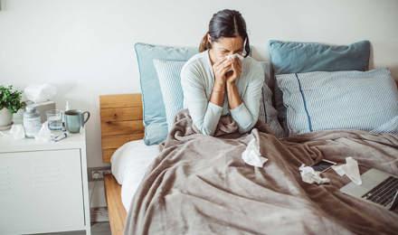 O femeie în pat își suflă nasul într-un șervețel