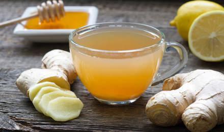 Ghimbir întreg și tocat, miere, lămâie și un pahar cu acestea amestecate, toate pe o masă de lemn