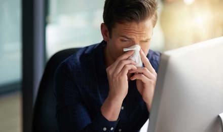 Un om strănutând în fața computerului, în timp ce caută perioada de incubație pentru răceli