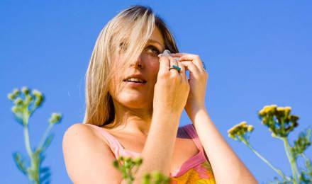 O femeie printre flori, vara, cu ochi iritați din cauza alergiei la polen