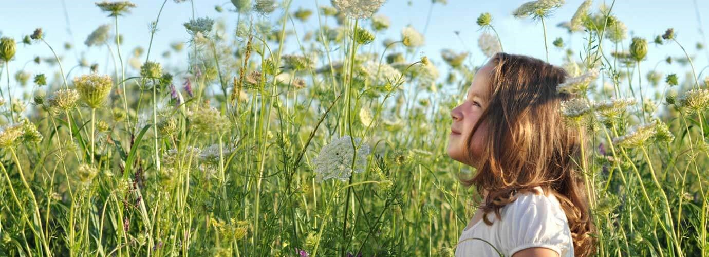 O tânără fată care ar putea avea nevoie de remedii pentru alergie la polen, aflându-se pe un câmp plin de flori inalte, sălbatice, într-o zi însorită