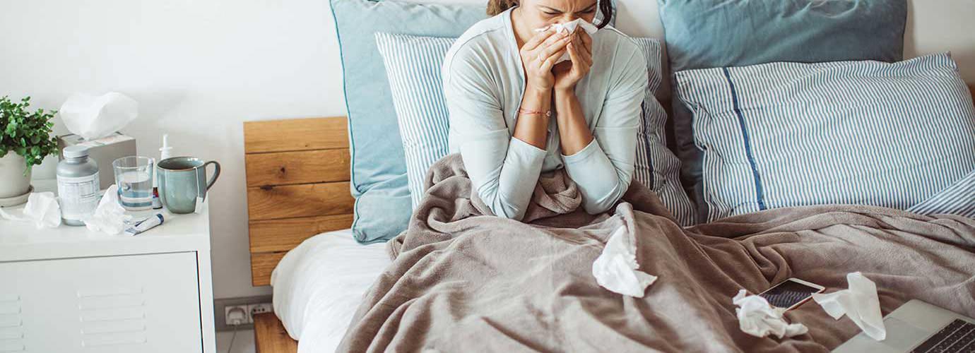 Žena u krevetu puše nos u maramicu