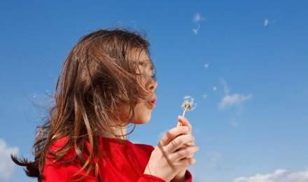 Malo dijete koje će možda trebati kućne lijekove za peludnu groznicu puše u maslačak s plavim nebom u pozadini