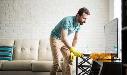 Ein Mann reinigt ein Haus durch Staubwischen