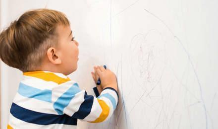 Ein kleiner Junge schreibt mit Stiften auf einer Tapete