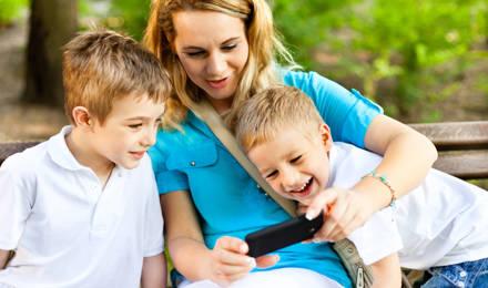 Žena sedící mezi dvěma malými chlapci, ukazující jim cosi na svém telefonu