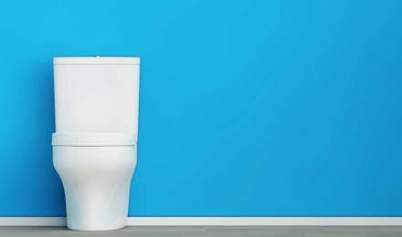 Čistá bílá toaleta před modrou zdí