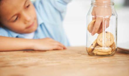 Ребенок дотягивается до стеклянной банки с печеньем на деревянном столе и берет печенье