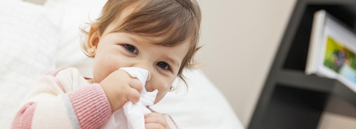 Маленькая девочка вытирает нос салфеткой