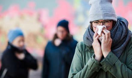 Женщина сморкается, и возможно хочет знать, как повысить иммунную систему, чтобы перестать сморкаться так часто