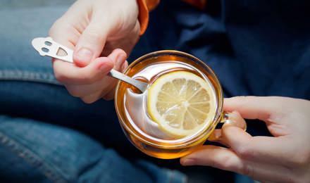 Человек держит стеклянную кружку, полную горячей воды, меда и лимона