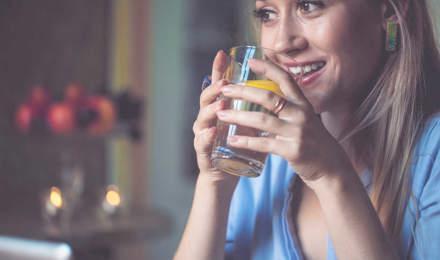 Женщина держит стакан воды с нарезанным лимоном в нем