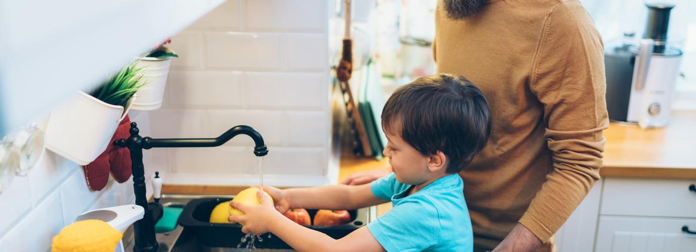 Мать помогает ее детям мыть руки на кухне