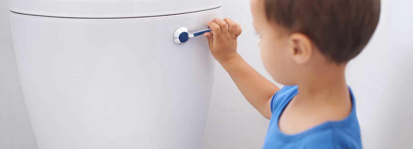 Malý kluk splachuje toaletu